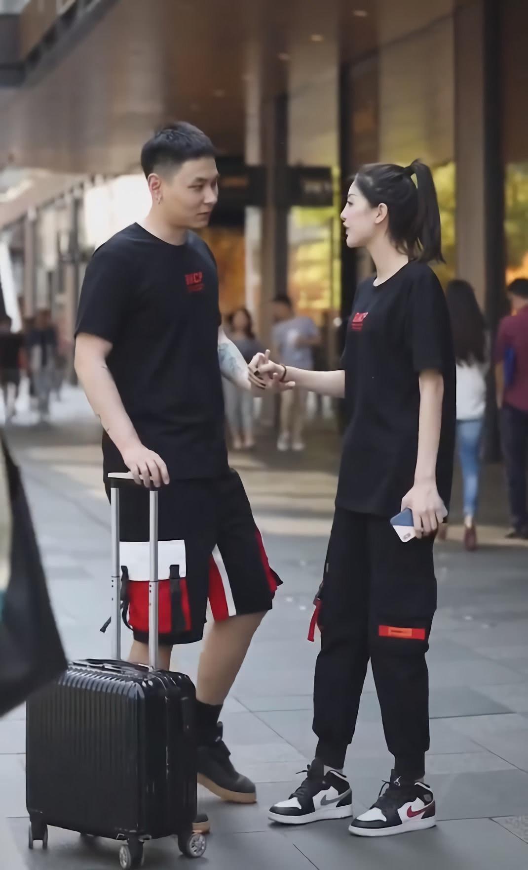 这对情侣真不怕热,一个穿AJ鞋配长裤,一个穿短靴配长袜子