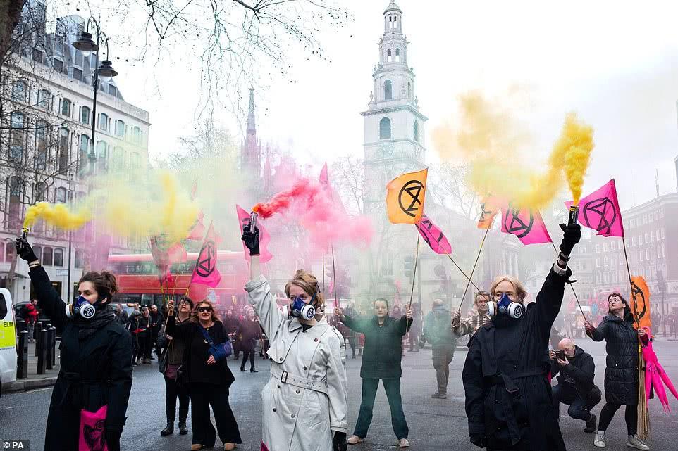 伦敦环保抗议者阻塞道路,放彩色烟雾,要求取消伦敦时装周,引司机愤怒