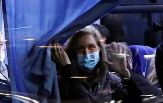 数百美国人乘大巴离开钻石公主号,透过车窗向外看并拍照,表情疲惫