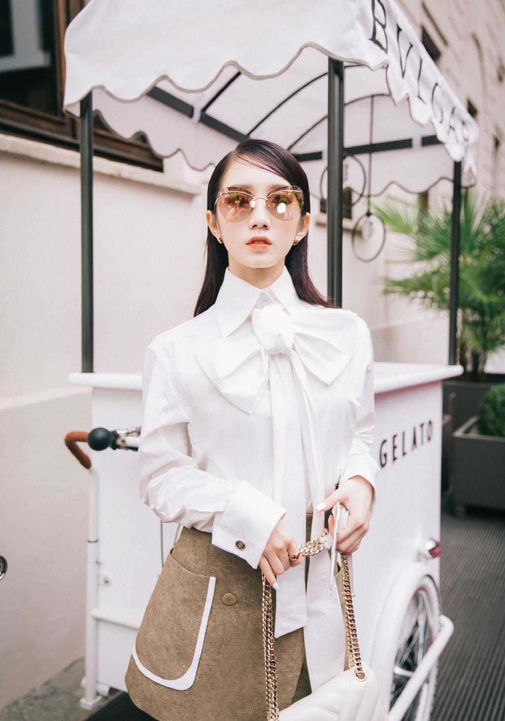 孟美岐美到国外了,穿大蝴蝶结白色衬衣配短裙,优雅又不失甜美