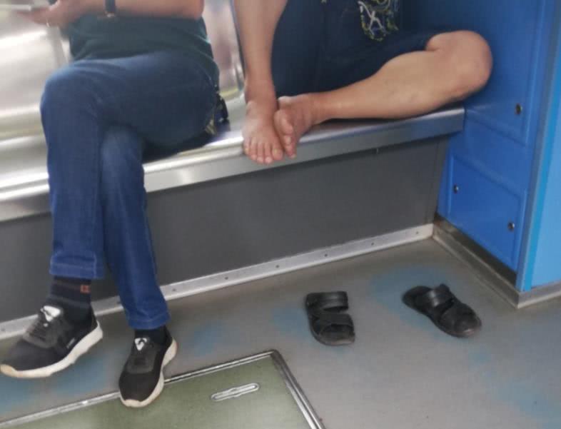 男子大热天赤脚踩在座椅上 毫不顾忌其他乘客的感受
