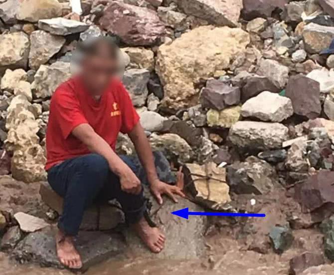 红衣男子坐江边欲轻生 双腿还拴着两块大石头