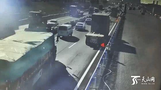 半挂车爆胎 高速交警手持三角警示牌步行护送出狭窄路段